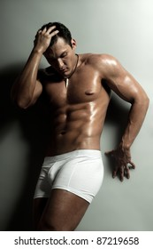 the very muscular handsome sexy guy on   grey background, strict