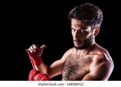a very muscular young boxer with red trunks and hand wraps over a dark background