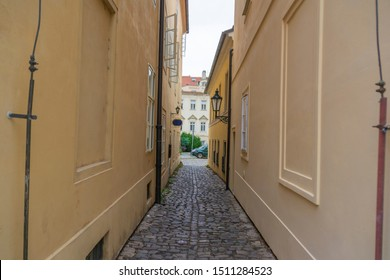 Very narrow aisle between houses facing the street on a sunny summer day