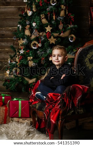 ad768b584fc1 Very nice boy sits near a Christmas tree smiling happily wrapped in a red  blanket