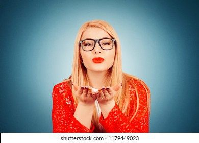 Very nice girl with brown eyes puckering lips giving a virtual kiss wearing red lace jacket and white formal shirt isolated on dark blue background with copy space and vignette. Horizontal image