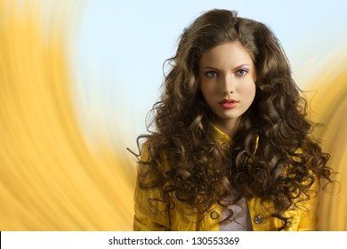 very nice and sexy fashion brunette girl with curly hair in a fantasy yellow and baby blue background