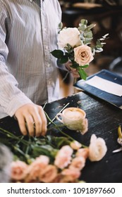 Very nice young florist man in a light blue shirt assembling a flower bouquet on the table using quicksand roses, mother conic peonies and eucalyptus