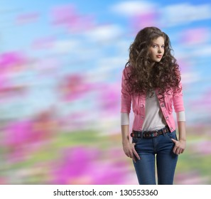 very nice young girl brunette with wavy and volume hair wears blue jeans and pink jacket, colorful background