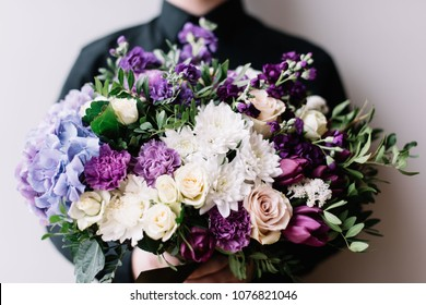 Very nice young man in a black shirt holding blossoming flower bouquet of fresh hydrangea, roses, carnations, eustoma, hyacinths in cosmic purple and blue colors on the grey wall background