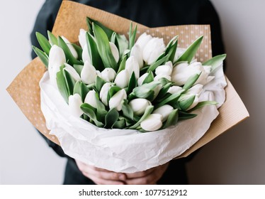 Very nice young man in a black shirt holding a huge blossoming flower bouquet of fresh white tulips on the grey wall background