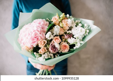 very nice young woman in a blue sweater holding a beautiful blossoming flower bouquet of fresh hydrangea, roses, carnations, mattiola, in pink and pastel cream colors on the grey wall background