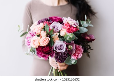 Very nice young woman holding a colourful fresh blossoming flower bouquet of roses, carnations, ranunculus and eucalyptus on the grey wall background