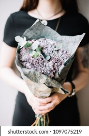 Very nice young woman holding a beautiful blossoming flower bouquet of fresh grey Black Molly carnations and eucalyptus in on the grey wall background