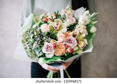 very nice young woman holding a beautiful blossoming flower bouquet of fresh green hydrangeas, quicksand roses, eustoma, pink roses on the grey wall background