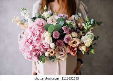 Very nice young woman holding beautiful tender blossoming bouquet of fresh hydrangea, eustoma, roses, eucalyptus flowers in pastel pink and cream colours on the grey wall background