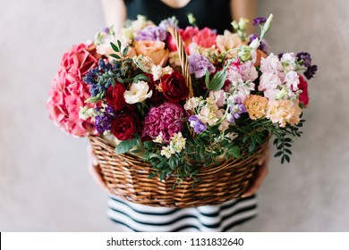 Very nice young woman holding beautiful wicker basket full of blossoming hydrangea, peonies, eustoma, mattiola, carnations, roses, pistachio leaves in different colours on the grey wall background