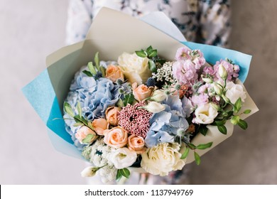 Very nice young woman holding beautiful blossoming flower bouquet of fresh hydrangea, roses, eustoma, mattiola, peony in blue, pink and white colors on the grey wall background