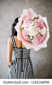 Very nice young woman holding huge fluffy beautiful blossoming bouquet of fresh hydrangea, roses, peony flowers in pink and white color on the grey wall background, standing back to the camera