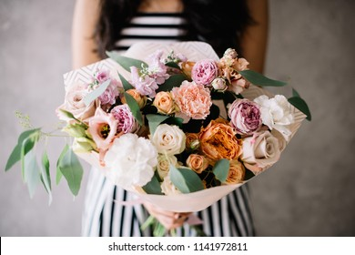 Very nice young woman holding beautiful blossoming bouquet of fresh peonies, roses, eustoma, carnations, eucalyptus flowers in pink and pastel cream colors on the grey wall background