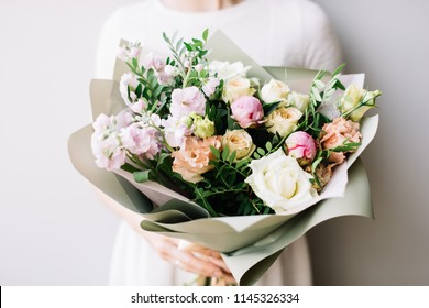 Very nice young woman holding beautiful blossoming bouquet of fresh roses, mattiola, eustoma flowers in pastel pink and cream colors on the grey wall background