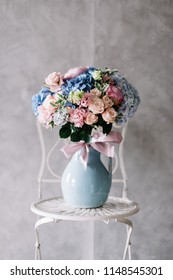 Very nice young woman holding beautiful blossoming bouquet of fresh roses, eustoma, hydrangea, peony, flowers in pink and blue colors in a vase standing on the chair on the grey wall background