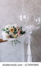 Very nice young woman holding beautiful blossoming bouquet of fresh dahlia, roses, mattiola, eucalyptus, eustoma flowers and one transparent festive balloon on the grey wall background