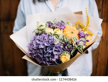 Very nice young woman holding beautiful blossoming bouquet of fresh flowers hydrangea, decorative little pumpkins, matthiola, roses in orange and purple colours on the grey wall background