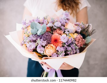Very nice young woman holding beautiful blossoming bouquet of fresh matthiola, peach Campanella roses, carnations, eucalyptus, dahlia flowers in peach and pastel purple colours