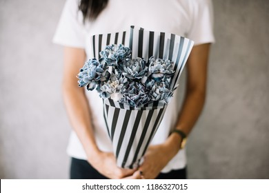 Very nice young woman holding big beautiful blossoming mono bouquet of fresh black molly and black Polly carnations in blue colors on the grey wall background