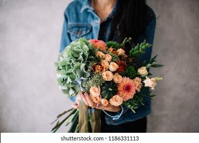 Very nice young woman holding big beautiful blossoming bouquet of fresh hydrangea, roses, cymbidium orchids, green trick carnations, green pumpkins, eustoma, nutan protea, dahlia, flowers