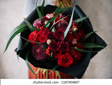 Very nice young woman holding big beautiful blossoming bouquet of fresh seasonal chrysanthemum, roses, gerbera, berries, flowers in vivid red colors on the grey wall background