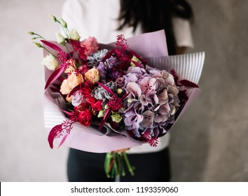 Very nice young woman holding big beautiful blossoming bouquet of fresh roses, hydrangea, eucalyptus, carnations, eustoma flowers in pink and purple colors on the grey wall background
