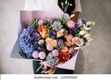 Very nice young woman holding big beautiful blossoming bouquet of fresh hydrangea, chrysanthemum, roses, eustoma, carnations, pistachio flowers in purple and orange colors on the grey wall background
