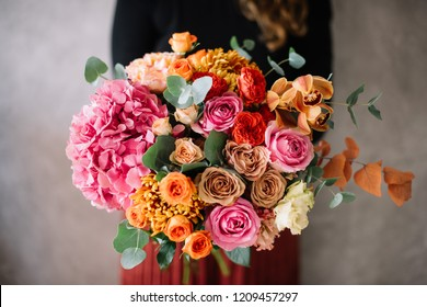 Very nice young woman holding big beautiful blossoming bouquet of fresh hydrangea, roses, carnations, chrysanthemums, cymbidium orchids, eustoma, eucalyptus flowers in pink, red and orange colors