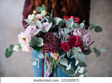 Very nice young woman holding big beautiful blossoming bouquet of fresh roses, chrysanthemum, eustoma, cinnerea eucalyptus flowers in lavender and purple colors on the grey wall background