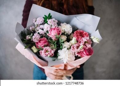 Very nice young woman holding big beautiful blossoming bouquet of fresh roses, matthiola, eustoma, carnations flowers in white and pink colors on the grey wall background