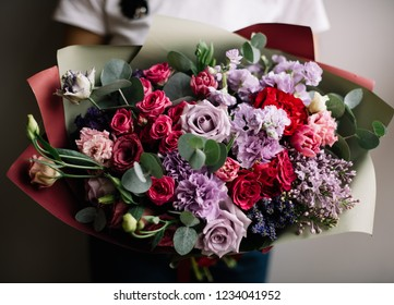 Very nice young woman holding big beautiful blossoming bouquet of fresh roses, matthiola, lisianthus, carnations flowers in red, pink, purple colors on the grey wall background