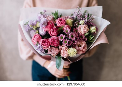 Very nice young woman holding big beautiful blossoming bouquet of fresh roses, matthiola, chrysanthemum, eustoma flowers in pastel lavender and pink colors on the grey wall background