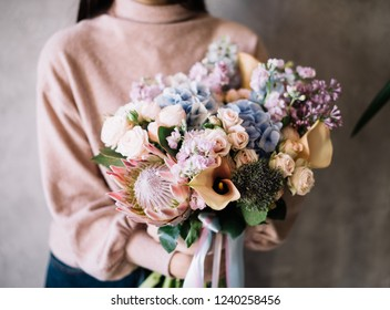 Very nice young woman holding big beautiful blossoming bouquet of fresh hydrangea, nutan protea, lilac, matthiola, roses, calla lilies flowers in blue, pink, cream and lilac colors
