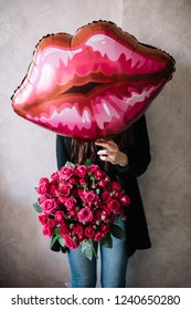 Very nice young woman holding big beautiful blossoming mono bouquet of fresh misty bubbles magenta roses and inflatable lips balloon on the grey wall background
