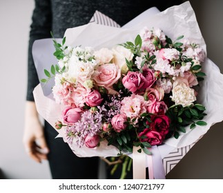Very nice young woman holding big beautiful blossoming bouquet of fresh roses, lilac, eustoma, matthiola, pistachio flowers in magenta and pastel pink colors on the grey wall background