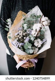 Very nice young woman holding beautiful blossoming bouquet of fresh cotton, eucalyptus, brunia flowers in colors on the grey wall background
