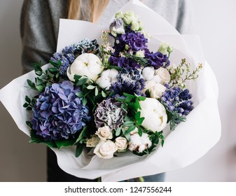 very nice young woman holding a beautiful blossoming flower bouquet of fresh hydrangea, peony, cotton, carnations, roses, eustoma, peony in white and blue colors on the grey wall background