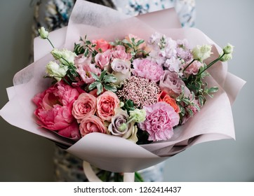 very nice young woman holding a beautiful blossoming flower bouquet of fresh peonies, roses, carnations, eustoma, matthiola in coral, pink and lavender colors on the grey wall background