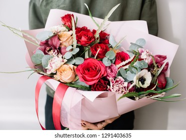 Very nice young woman holding beautiful blossoming bouquet of fresh roses, eucalyptus, cymbidium orchids, carnations, examine flowers in red and pink colors on the grey background