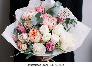 Very nice young woman holding big and beautiful blossoming bouquet of fresh david austin roses, roses, peony, gorse, tulips, eucalyptus flowers in white and pink colors on the grey wall background