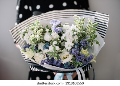 Very nice young woman holding big and beautiful bouquet of fresh limonium, eustoma, mathtiola flowers in white and purple colors on the grey wall background