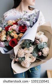 Very nice young woman holding two beautiful blossoming flower bouquets of fresh roses, ranunculus, tulips, mattiola, eucalyptus, carnations in red, purple, pink colors on the grey wall background