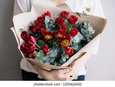 Very nice young woman holding a beautiful blossoming mono beyonce tulips and eucalyptus bouquet in red colors on the grey wall background