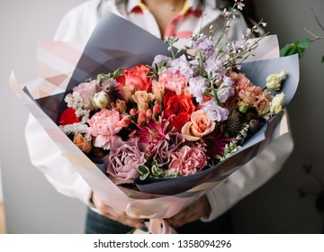 Very nice young woman holding huge beautiful blossoming bouquet of fresh roses, gerbera, carnations, eustoma, matthiola, genista, statice in red and purple colors on the grey background
