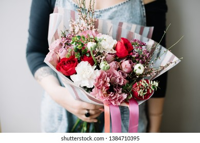 Very nice young woman holding huge beautiful blossoming bouquet of fresh roses, ranunculus, carnations, eustoma genista in red white and pink colors on the grey background
