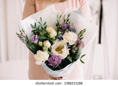 Very nice young woman holding beautiful blossoming bouquet of fresh  carnations, ranunculus, roses, eustoma, pistachio in white and purple colors