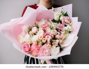 Very nice young woman holding huge beautiful blossoming bouquet of fresh roses, eustoma, carnations, calla lilies. statice in white and pink colors on the grey background