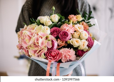 Very nice young woman holding huge beautiful blossoming bouquet of fresh hydrangea, carnations, roses, eustoma in pink colors on the grey background